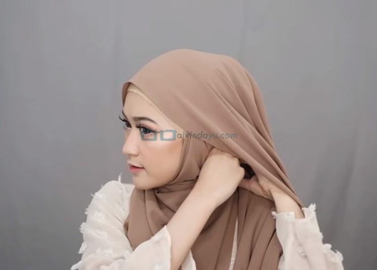 Tutorial Hijab Pashmina Simple Menutup Dada untuk Wajah Bulat, Bawa ke Samping Sisi Hijab yang Dikedepankan dan Sematkan Jarum Pentul
