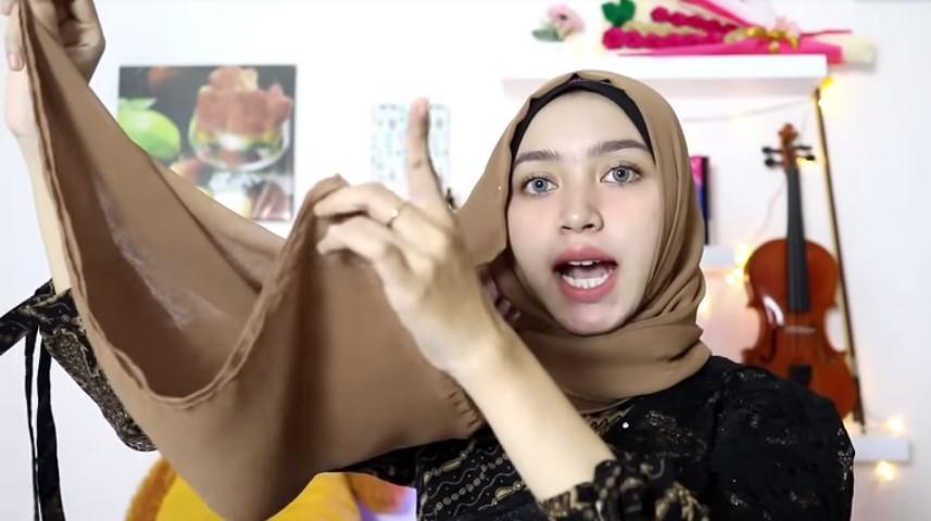 Tutorial Hijab Pesta Elegan Segi Empat, Pegang Sisi Hijab Panjang di Bagian Bawahnya dan Lepaskan Bagian Atasnya